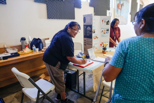 At right, Maxine Tsosie, a community health worker with the Navajo Nation Department of Health talks provides information on health screenings to community members, Friday, Sept. 21. 2018 during the Nenahnezad Harvest Festival at the Nenahnezad Chapter House in Fruitland.