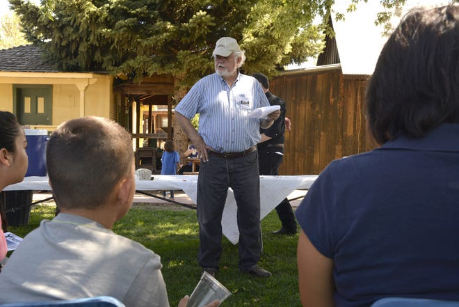 Aztec Board Member Dale Anderson talks to a group about planting Saturday, September 20, 2014 during Founders Day at Aztec Museum in Aztec.