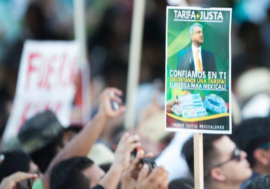 """A sign demanding better electrical rates is seen in the crowd as Mexico's President-elect, Andres Manuel Lopez Obrador arrives at Mexicali's Civic Center on September 20, 2018 during his """"Gratitude Tour"""" to the capital of Baja California."""