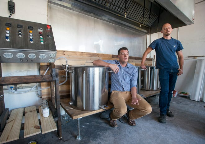 From left, co-owners Nick Holmes and Dallas Cook talk Thursday about plans for their Beardless Brewhaus brewery at the site of the former Main Street Cafe and Courtyard Bar in downtown Milton.