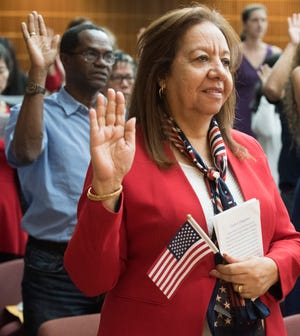 Lillian Sobhy Ghaly Abdelmalek takes the oath of citizenship with 75 other new U.S. citizens during a naturalization ceremony Friday at City Hall.