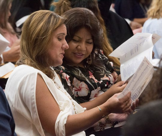 Maria Alejandra Johnson Long and Anita Cortez Kent search for their names in the program at a naturalization ceremony Friday at City Hall. Long immigrated from Venezuela and Kent from Mexico.