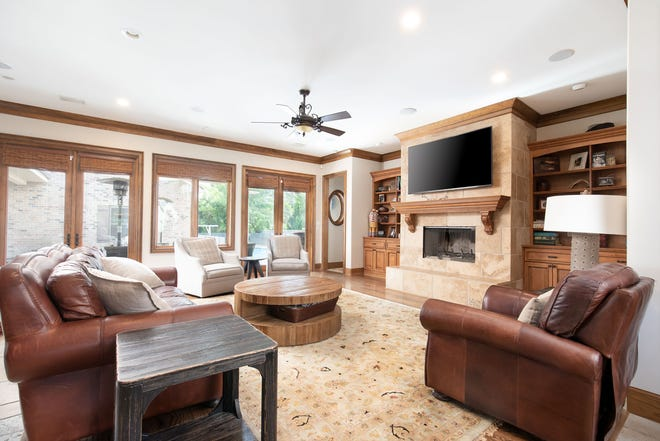 1329 Quiet Cove Court, the living room includes an elegant fireplace and access to the rear patio and pool deck.
