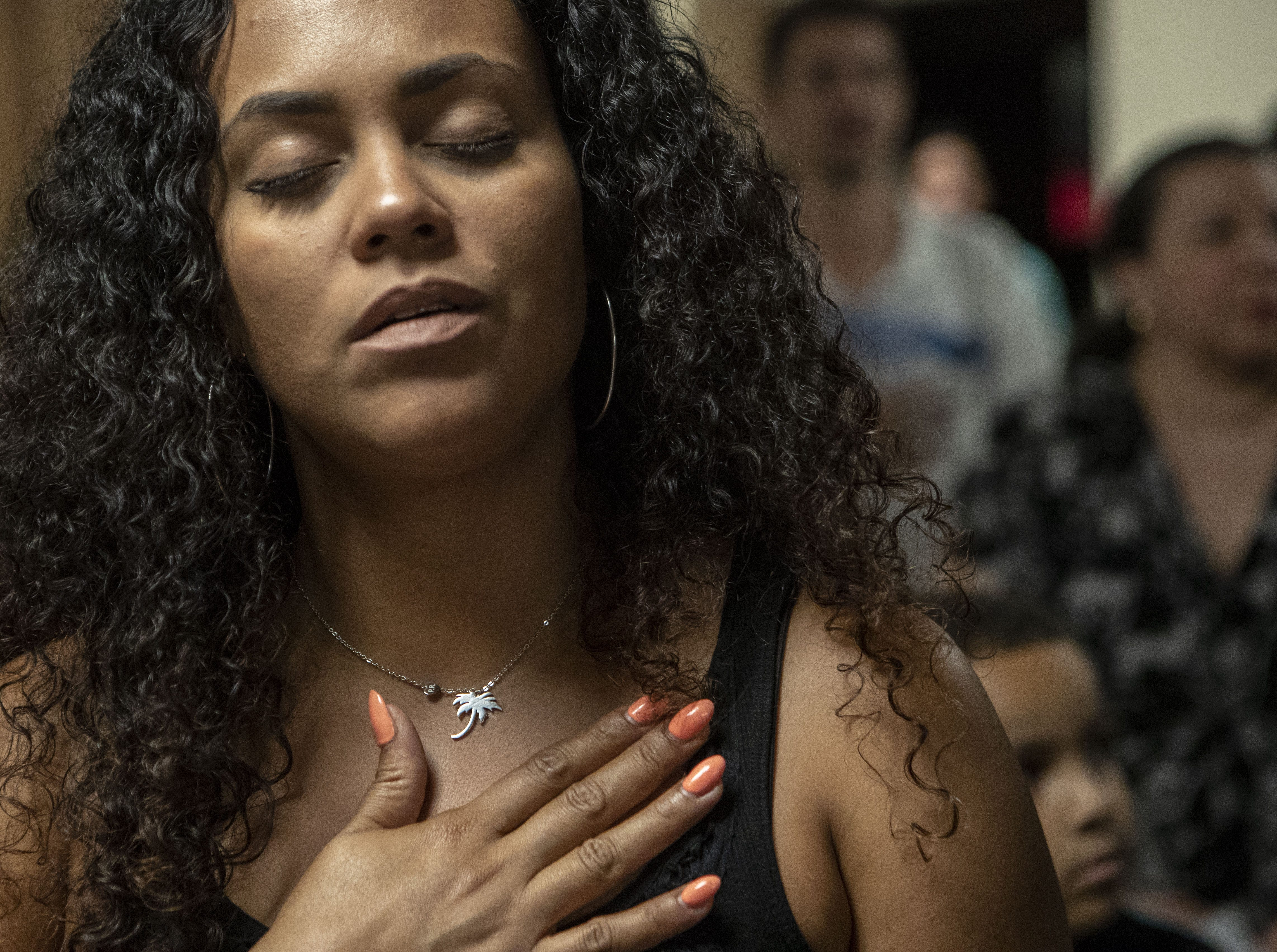 Germaine Ortiz, 33, from Arroyo, Puerto Rico, marks the one-year anniversary of Hurricane Maria during a service in Phoenix. The service remembered the nearly 3,000 people who died in the hurricane's aftermath and honored survivors, including those who lived through the storm, those forced to abandon the island, and those on the mainland cut off from relatives and friends.