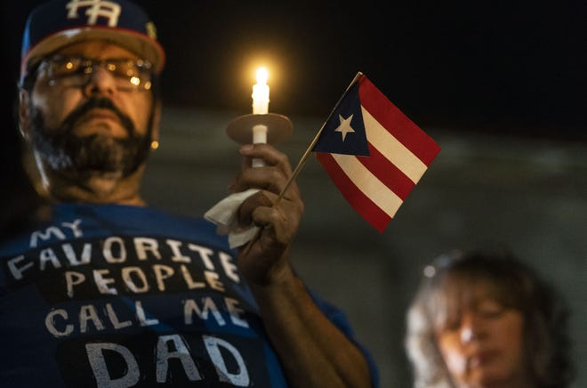 Wally Correa holds a candle and Puerto Rican flag at the Phoenix service to commemorate the one-year anniversary of Hurricane Maria.
