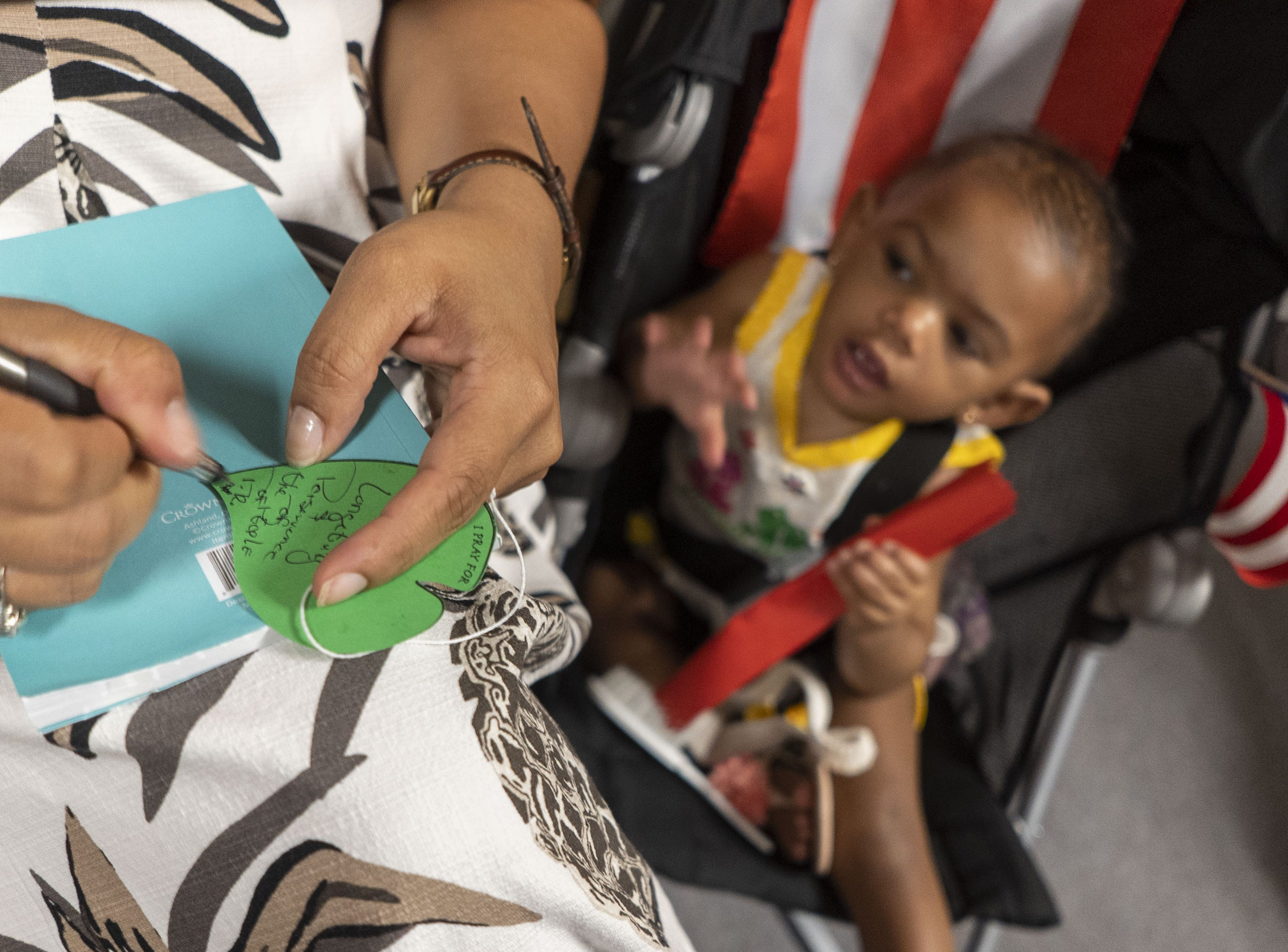 A woman writes a note on a piece of green paper shaped like a leaf to place on a prayer tree during a service commemorating the one-year anniversary of Hurricane Maria. The hurricane-force winds  stripped trees bare turning the green island brown, but the leaves are growing back, said Gretchen Patterson, president of the Puerto Rican Center of Arizona.