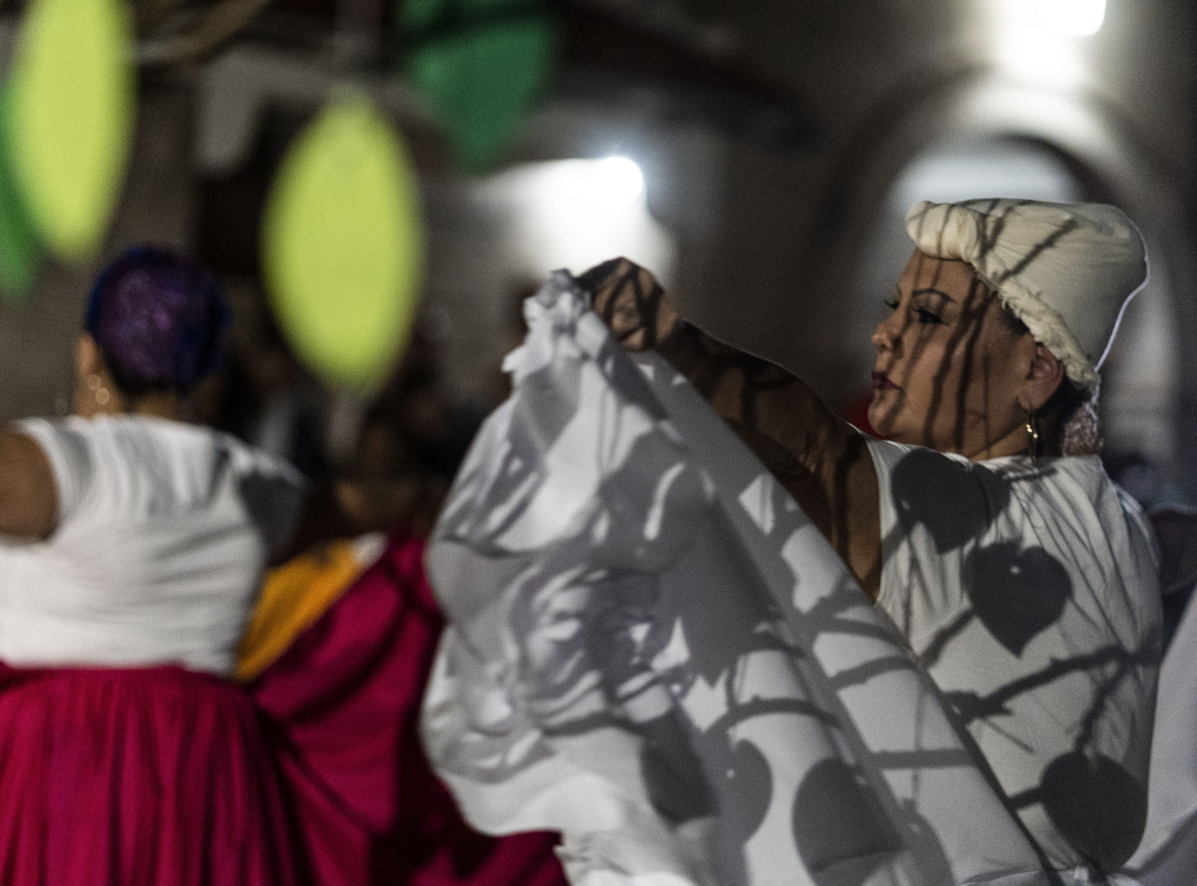 Puerto Ricans marked the anniversary of Hurricane Maria by writing notes on pieces of green paper shaped like leaves and hanging them on a prayer tree in the courtyard of Faith Evangelical Lutheran Church in Phoenix. The leaves cast shadows on folkloric dancers who performed at the end of the three-hour service.
