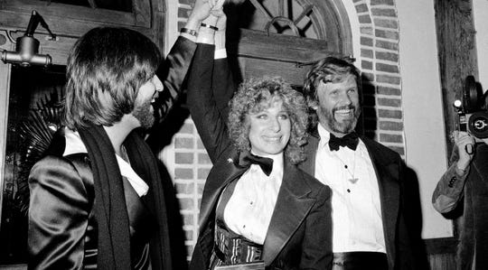 """Barbra Streisand and Kris Kristofferson (right) attend a screening of """"A Star Is Born"""" on Dec. 23, 1976, in New York City. Producer (and Streisand's former boyfriend) Jon Peters holds her hand."""