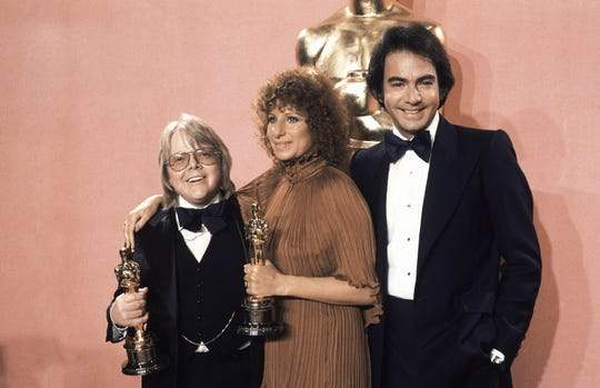 Barbra Streisand and Paul Williams hold the Oscars they won backstage at the Academy Awards on March 28, 1977. Neil Diamond presented the two with their trophies.