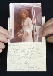 """In a 2006 photo, Tina Barajas shows her picture of Barbra Streisand snapped during the making of """"A Star Is Born,"""" along with a thank-you note she later received from the star."""