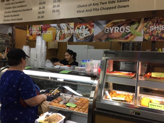 Mai Elhabashy takes a customer's order on opening day Mediterranean Foods.