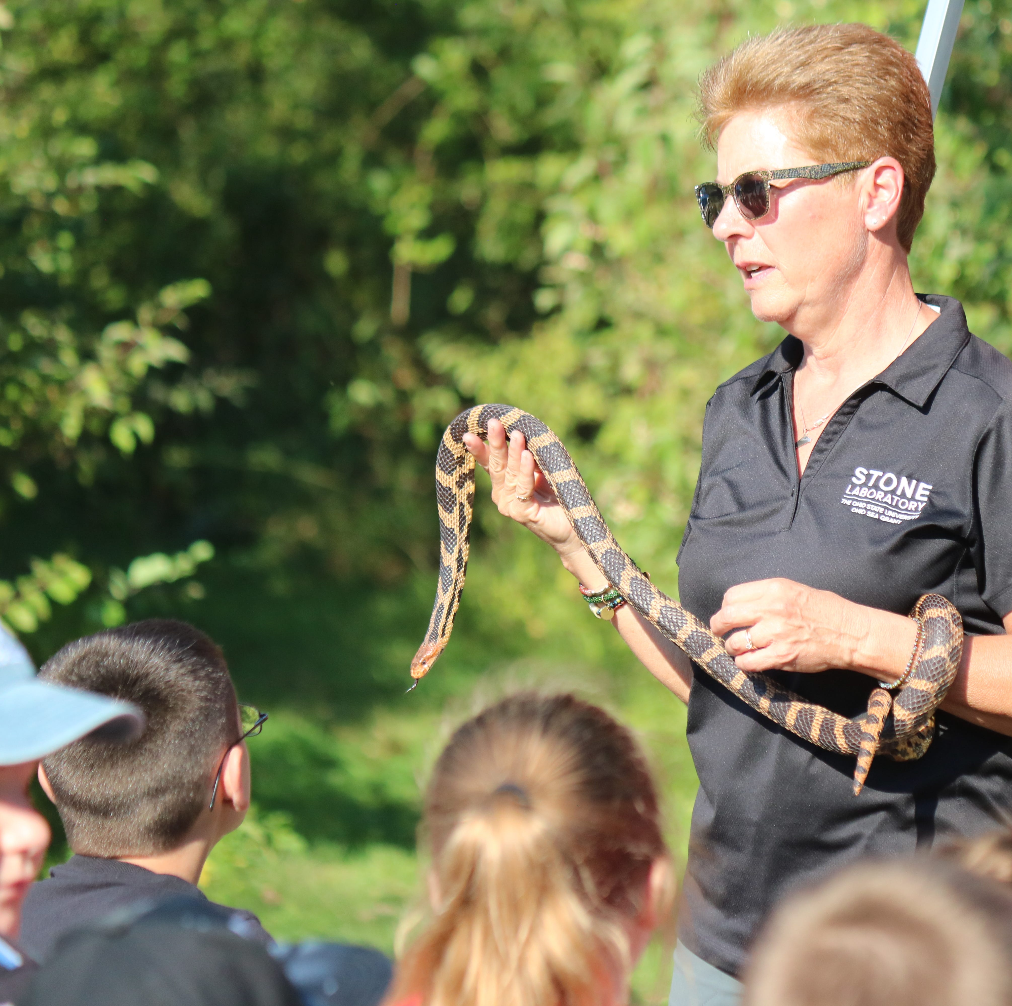 Sue Bixler, of Ohio State's Stone Lab, shows students an eastern foxsnake, species of concern in Ohio, during the 57th annual Fifth Grade Conservation Field Day.