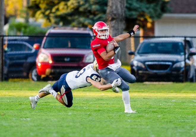 Port Huron High School quarterback Johnny Oriel is grabbed by Grosse Pointe South High School running back Brady McCarron as he runs with the football Friday, Sept. 21, 2018 during their game at Memorial Stadium.