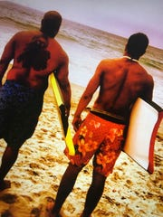 "His name means ""courageous warrior"" in Hawaiian. Koa Farmer, right, grew up boogie boarding the biggest waves he could find along his mother's home island. Here, he prepares to go for a ride with his father, Jamal."