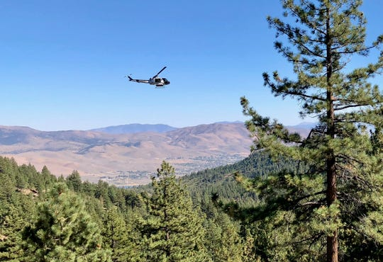 The Washoe County Sheriff's Department RAVEN helicopter searches for a missing woman off Mount Rose Highway on Friday afternoon, Sept. 21, 2018.