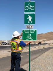 An RTC crew member installs a sign designating a path as the Erica Greif Bike Path.