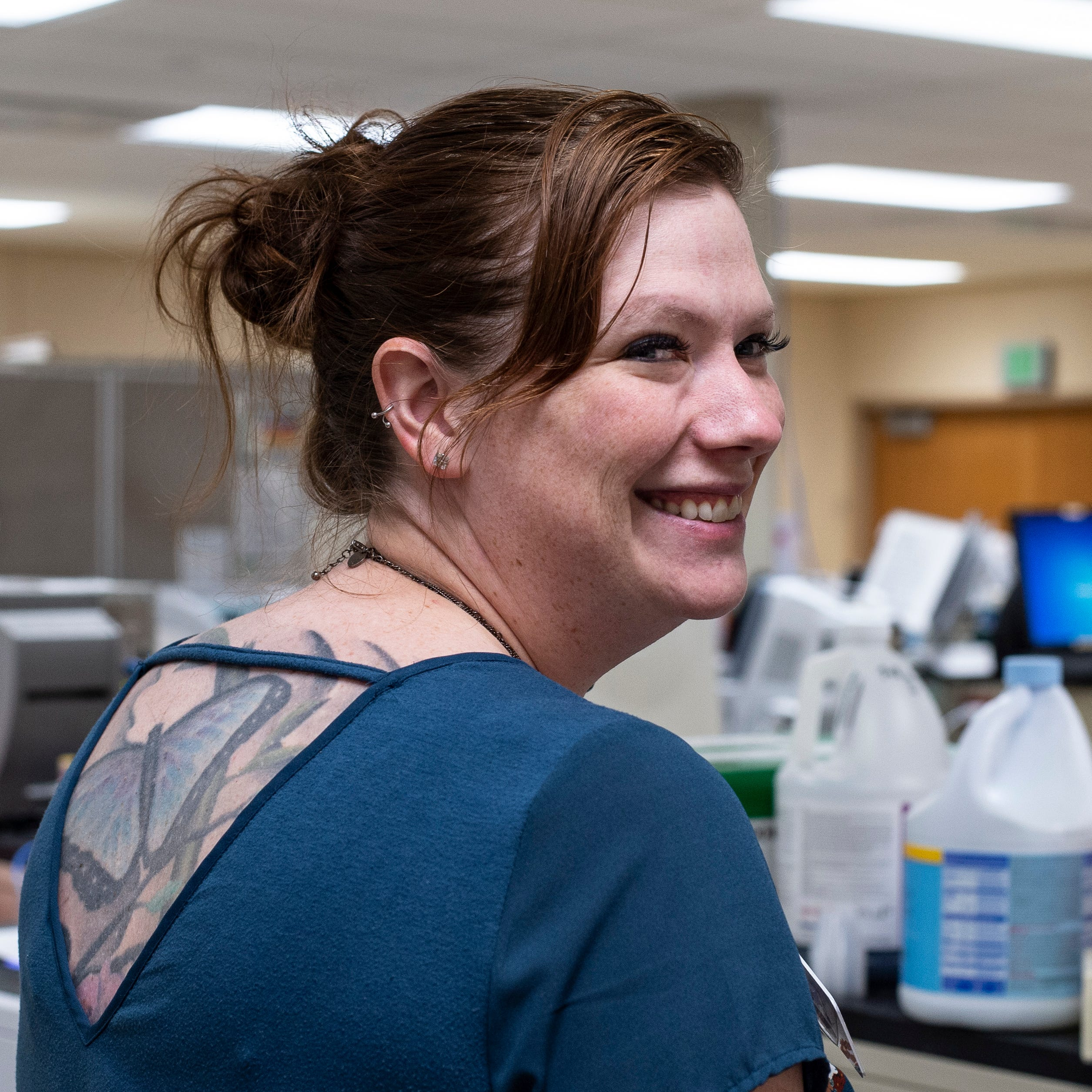 Reid Health lab manager Diana Eastman poses for a photo in the hospital's laboratory on Friday, Sept. 21, 2018. The tattoo on Eastman's back is now permitted to be visible following a change to the hospital's policy on the matter earlier in the year.