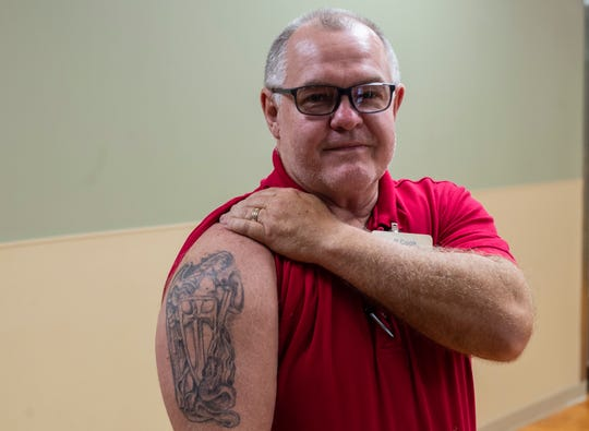 Reid Health employee Jeff Cook poses for a photo showing his tattoo in a hallway at the hospital on Friday, Sept. 21, 2018.