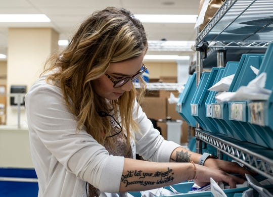 Reid Health pharmacy technician Taylor Brownell searches for a patient's order in the hosptial's pharmacy area on Friday, Sept. 21, 2018. Her tattoos are permitted to be visible following a change in Reid's policy on the matter earlier this year.