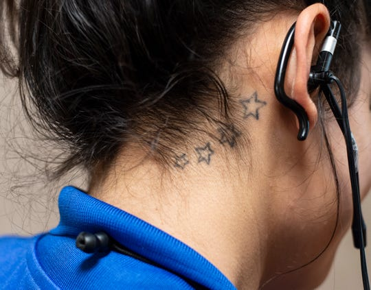 Reid Health Food & Nutrition Services employee Kurstie Gribben's tattoo behind her ear is seen inside the hospital on Friday, Sept. 21, 2018.