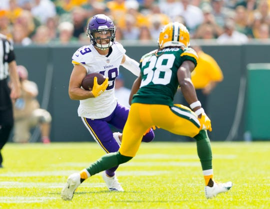 Minnesota Vikings wide receiver Adam Thielen (19) runs with the football after catching a pass as Green Bay Packers cornerback Tramon Williams (38) defends during the second quarter at Lambeau Field.