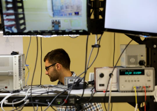 David Calhoun works in a lab at Precision Optical Transceivers with photonics technology.