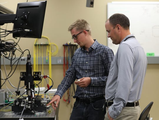 Precision Optical Transceivers CEO Todd Davis, right, and Nathan Rummage look at a chip on a microscope that uses photonics to help transfer information.