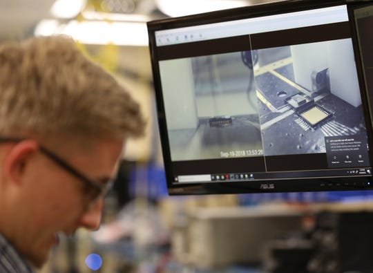 Nathan Rummage looks at a chip on a microscope that uses photonics to help transfer information.