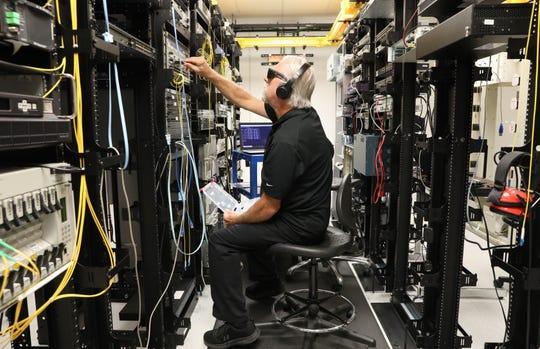 Dennis Brown checks quality-control data on transceivers at Precision Optical.