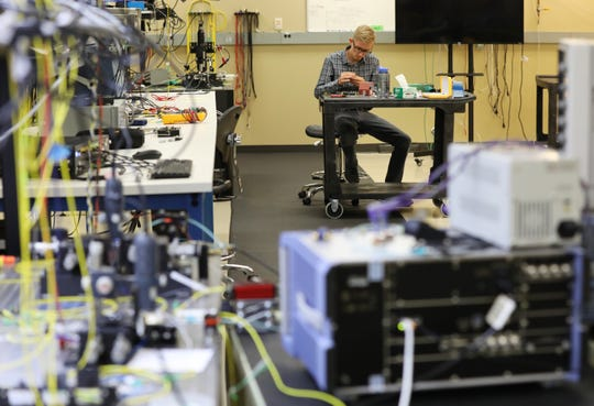 Nathan Rummage works on small tools that he is using on a microscope that's holding a micro chip that uses photonics to help transfer information.