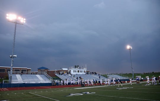 The West Irondequoit Eagles leave the field at Victor after a lightning delay prior to Friday night's game. The game was eventually postponed.
