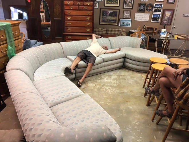 Nels Klaseen, volunteer at CARR Furnishings, test-drives a living room couch set. CARR Furnishings provides donated furniture to people in new homes after they lost their homes in the Carr and Delta fires.