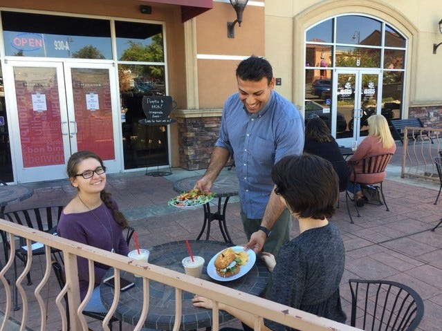 Madayne owner Ahab Alhindi serves lunch to Ashley Santos, left, and April Kwiatkowski at his Hilltop Drive restaurant.