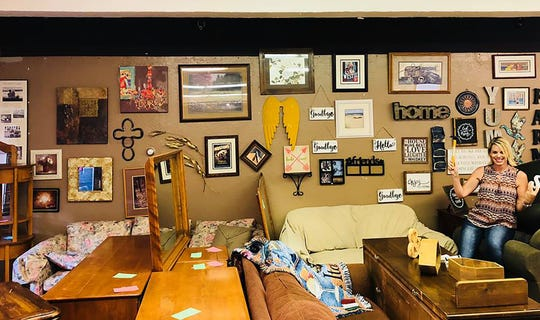 Joy Gaskey, volunteer at CARR Furnishings, sits next to the Wall of Joy; wall decor donated for use by people rehomed after they lost their homes in the Carr and Delta fires.