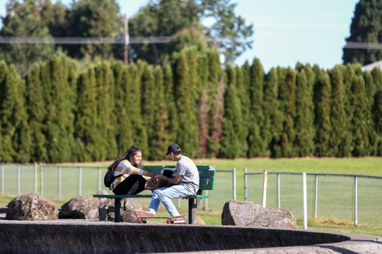 McKay High School juniors Gabriela Juarez and Jesus Arredondo hang out at the community park near the school on Thursday, Sep. 20. Salem Parks Foundation is raising money to purchase McKay Park new playground equipment.