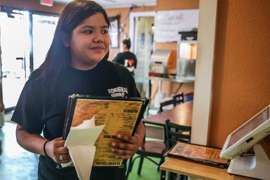 Nalleli Lira, 17, take menus to a table Thursday, Sept. 20, 2018, at Mendez Cafe in San Angelo.