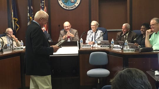 Carter Crabbe looks at a plaque bearing a resolution passed in his honor by the Accomack County Board of Supervisors on Wednesday, Sept. 19, 2018 in Accomac, Virginia.