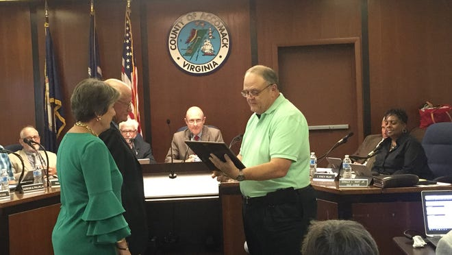 Carter Crabbe, second from left, listens as Supervisor Donald L. Hart Jr. reads a resolution of the Accomack County Board of Supervisors in Crabbe's honor on Wednesday, Sept. 19, 2018 in Accomac, Virginia.