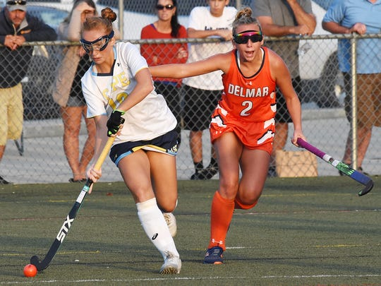 Capes Maci Long moves the ball past Delmar's Morgan Bradford as Cape Henlopen HS (white) hosted Delmar HS (orange) in Varsity Hockey at Champions Field at the school near Lewes on Thursday, September 20th. Special to the Daily Times / CHUCK SNYDER