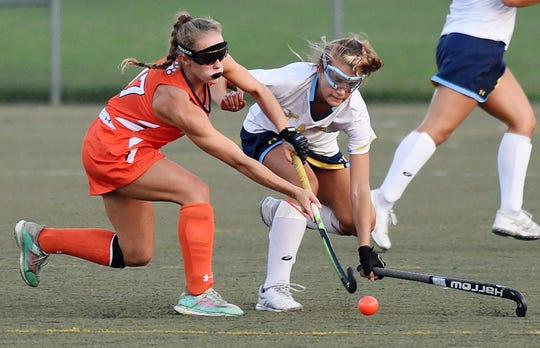 Delmar's Ashlyn Carr and Capes Alia Marshall fight over the ball as Cape Henlopen HS (white) hosted Delmar HS (orange) in Varsity Hockey at Champions Field at the school near Lewes on Thursday, September 20th. Special to the Daily Times / CHUCK SNYDER