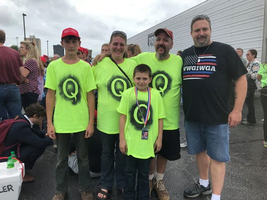 Aaron and Darcy Kendall pose with David Clardy for a photo while wearing their QAnon shirts.