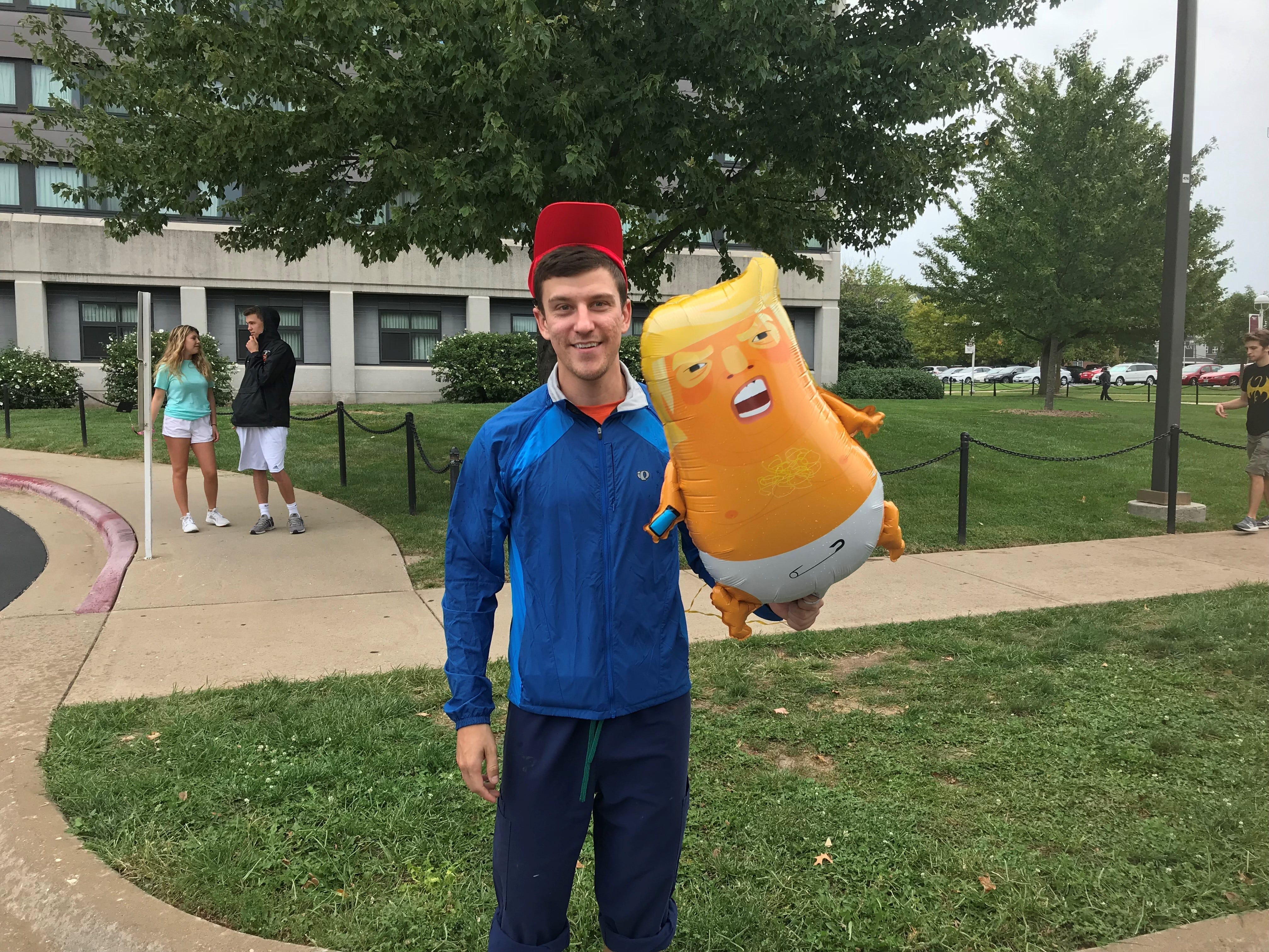 Joe McGreevy said someone handed him a baby Trump balloon. He says he doesn't support the president but isn't here to protest him. He hopes to attend the rally to satisfy his curiosity.