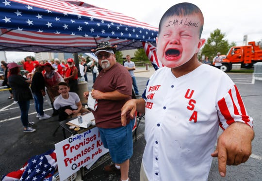 Randal Thom wears a mask and pretends to be a crying liberal baby while waiting in line outside of JQH Arena on the campus of Missouri State University to hear President Donald Trump speak on Friday, Sep. 21, 2018.