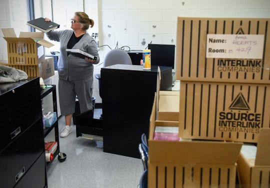 Teacher Anna Heerts, economics and U.S. history, moves back into her classroom Friday, Sept. 21, at Apollo High School. A fire damaged the school during remodeling this summer.