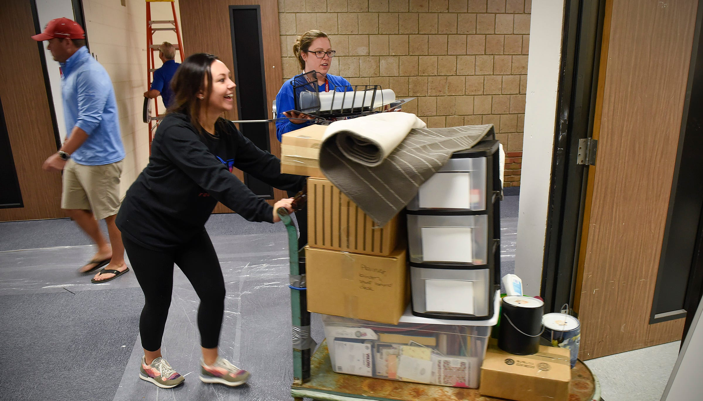 Teacher Katie Dorn, special education, moves back into her room with help from Vanessa VanLaanan, language arts, Friday, Sept. 21, at Apollo High School. The entire student body will return to school on a full-time basis Monday.