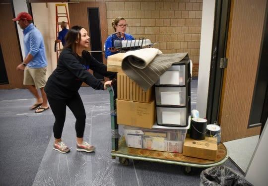Teacher Katie Dorn, special education, moves back into her room with help from Vanessa VanLaanen, language arts, Friday, Sept. 21, at Apollo High School. The entire student body will return to school on a full-time basis Monday.