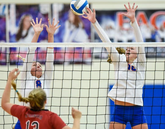 Apollo's Olivia Hoeschen and Haley Schleper try to block a spike by Alexandria's Kendra Hardy during the third game Thursday, Sept. 20, at Apollo High School.