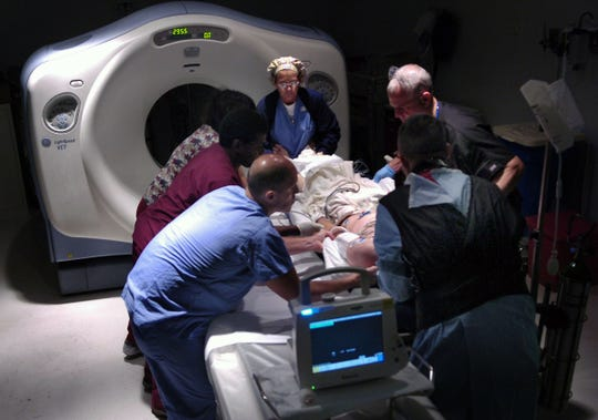 Trauma surgeon Dr. Alex Funicello, front left, and the staff of paramedics and technicians lift a vehicle crash patient into the bed for a CT scan while being treated at Lawnwood Regional Medical Center & Heart Institute's trauma center in 2009.