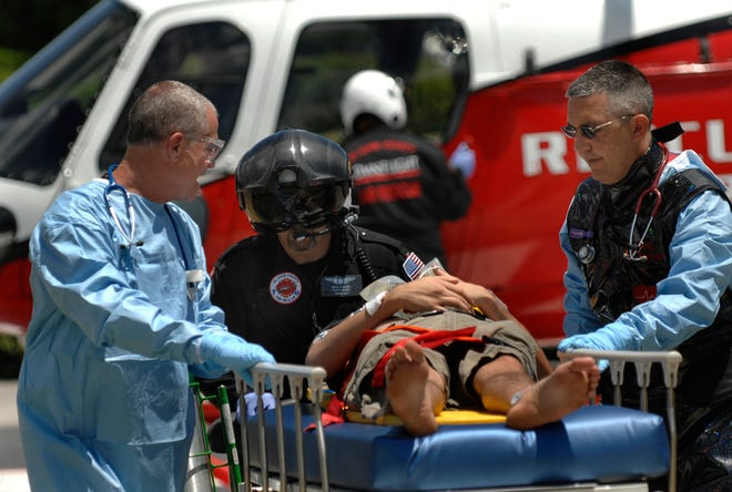 Paramedics Greg Wadley RN, left, and Gess Pantley, right, receive a patient involved in a vehicle crash in Vero Beach from Omniflight Air Rescue staff at the helicopter pad at Lawnwood Regional Medical Center & Heart Institute in Fort Pierce for treatment at Lawnwood's trauma center in 2009.