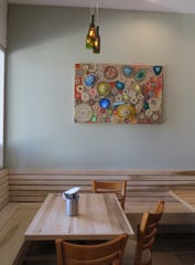 Wine-bottle chandeliers by owner Graham Harris and artwork made from recycled materials by Oak Park High School students are part of the decor at Decker Kitchen in Westlake Village.